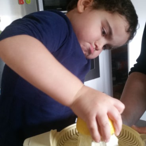 little boy squeezing lemon juice with a look of concentration on his face