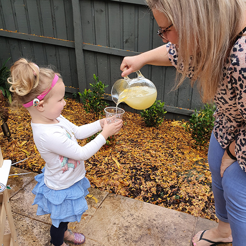 lady pouring lemonade from a jug into little girl's cup