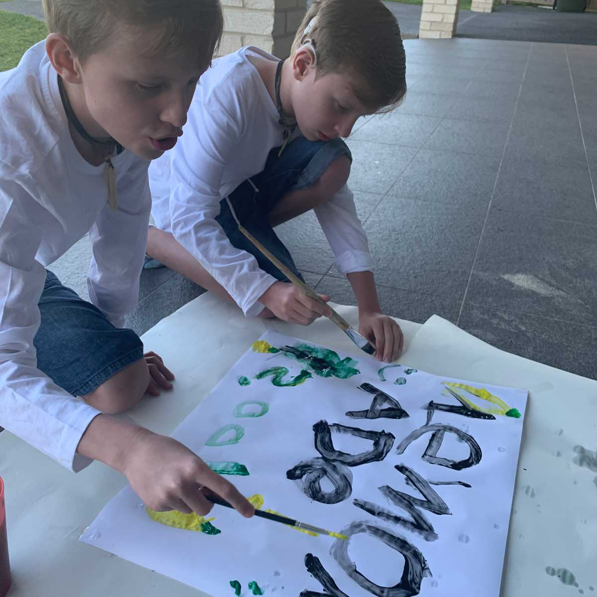 2 twin boys making a lemonade stand sign with yellow and green paint