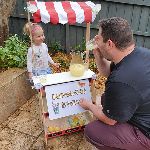 little girl behind her lemonade stand smiling while man drinks his lemonade