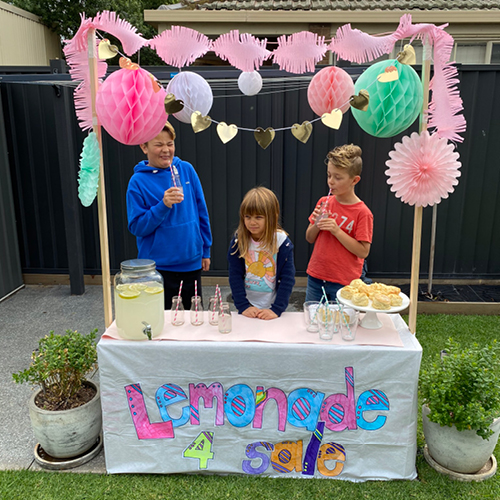 3 kids standing in their backyard with their homemade lemonade stand, sipping lemonade. One boy with a sour look on his face from the lemons