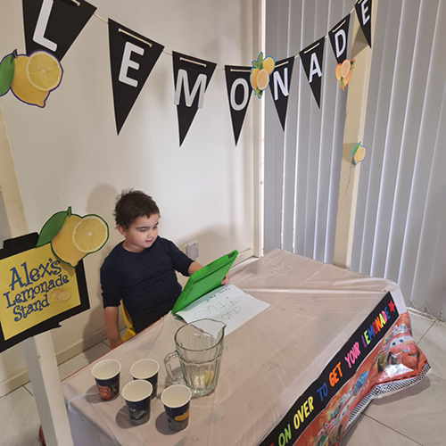 a boy named Alex sitting in his homemade lemonade stand